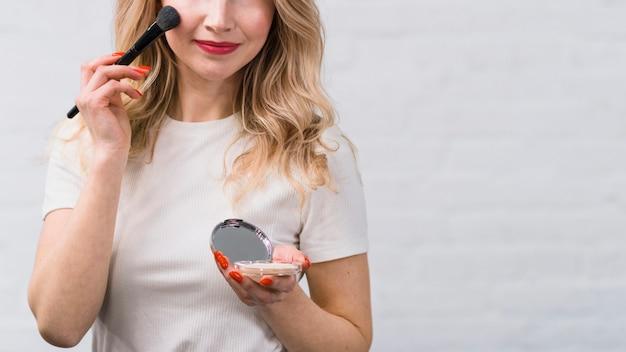 Mujer con el pelo rubio sosteniendo polvo haciendo maquillaje