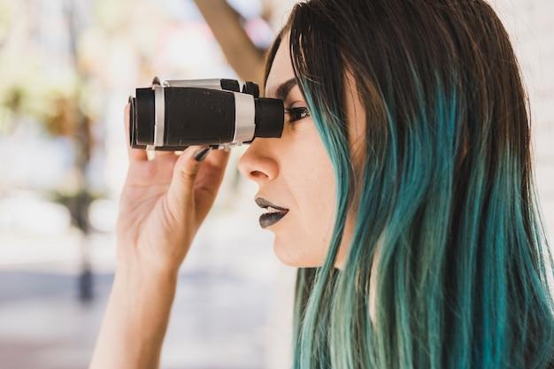 Una mujer con el pelo teñido mirando a través de binoculares.
