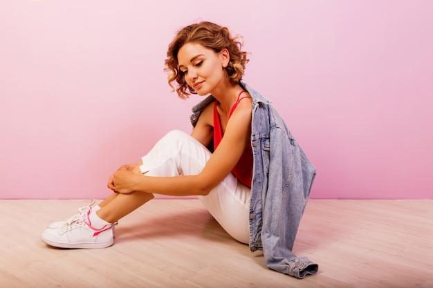 Mujer con pelos ondulados cortos sentados en el suelo sobre rosa