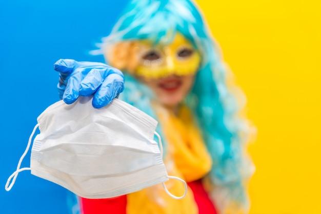Una mujer con una peluca azul, una máscara de carnaval amarilla y guantes médicos sostiene una máscara de salud de la corona de virus en la mano.