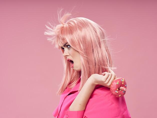 Mujer con una peluca rosa, ropa sobre un fondo rosa con comida