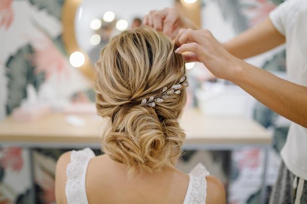 Mujer de peluquería tejiendo trenzas, peinado de boda.
