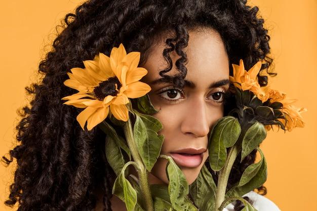 Mujer de pensamiento étnica atractiva con flores
