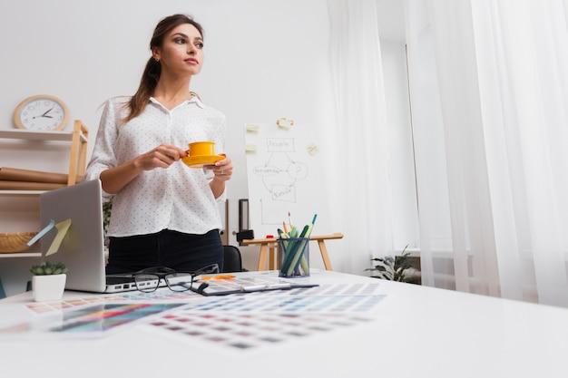 Mujer de pensamiento que sostiene una taza de café