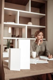 Mujer pensando. mujer rubia pensando en pedir el almuerzo en su habitación de hotel durante un viaje de negocios