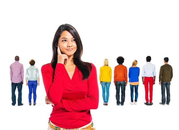 Mujer pensando con personas diversas detrás de ella