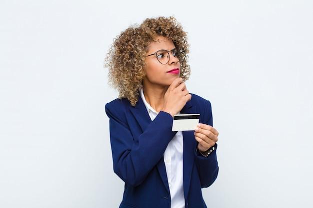 Mujer pensando, sintiéndose dudosa y confundida, con diferentes opciones, preguntándose qué decisión tomar