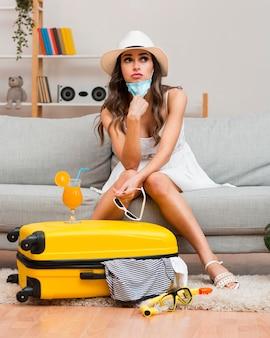Mujer pensando en sus vacaciones pospuestas junto a su equipaje