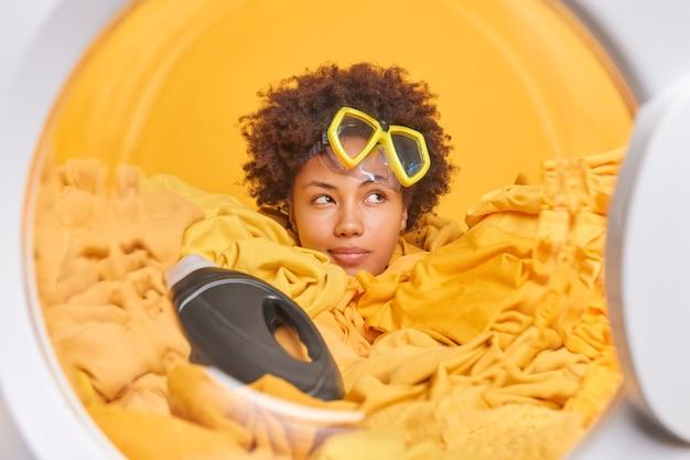 Mujer pensativa asoma la cabeza a través de la pila de poses de ropa en la lavadora ocupada con el servicio de limpieza, usa polvo líquido, usa máscara de snorkel, mira hacia otro lado, prepara el ciclo de lavado