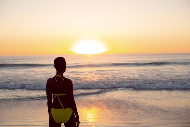 Mujer pensativa en bikini de pie en la playa