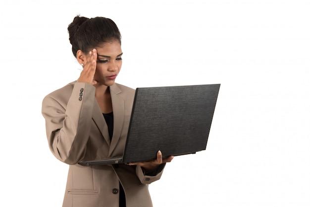 Mujer pensativa con una computadora portátil - aislada sobre un espacio en blanco
