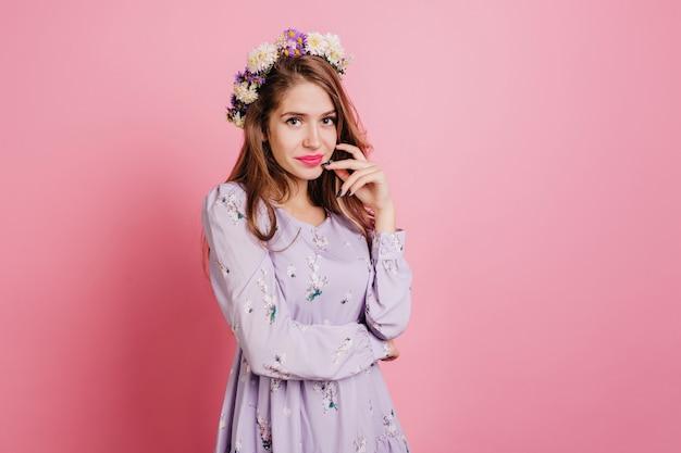 Mujer pensativa en corona de flores posando en la pared rosa