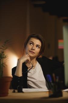 Mujer pensativa diseñadora en el trabajo