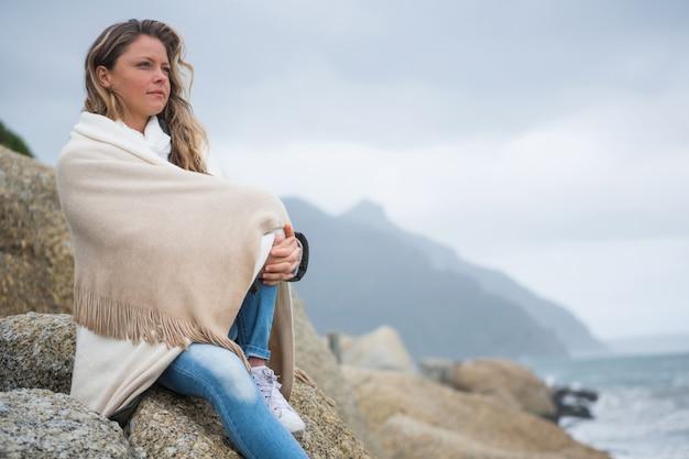 Mujer pensativa envuelta en chal sentado en las rocas