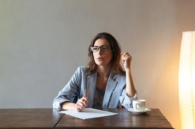 Mujer pensativa escribiendo notas.