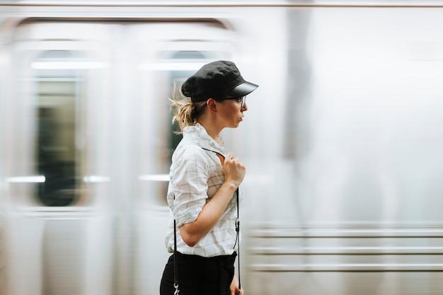Mujer pensativa esperando un tren en una plataforma de metro