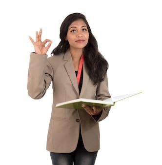 Mujer pensativa estudiante, maestra o mujer de negocios sosteniendo libros y mostrando un signo bien en el espacio en blanco