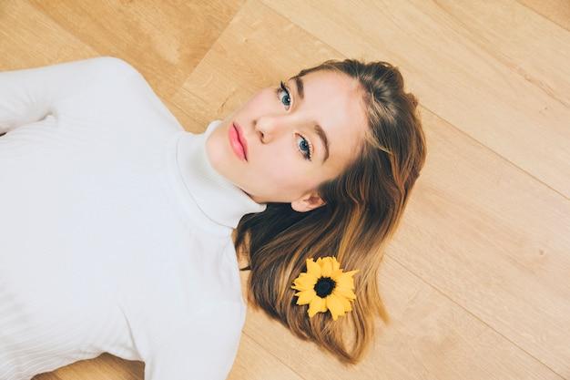 Mujer pensativa con la flor en el pelo que miente en piso