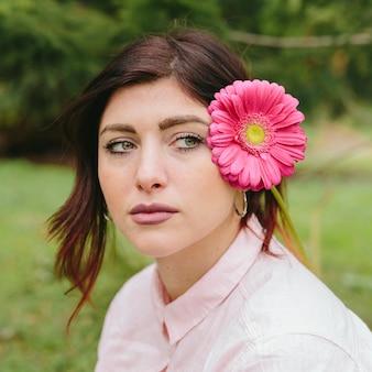 Mujer pensativa con flor en el pelo