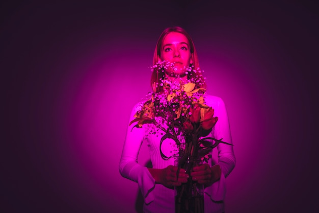 Mujer pensativa con flores brillantes en florero