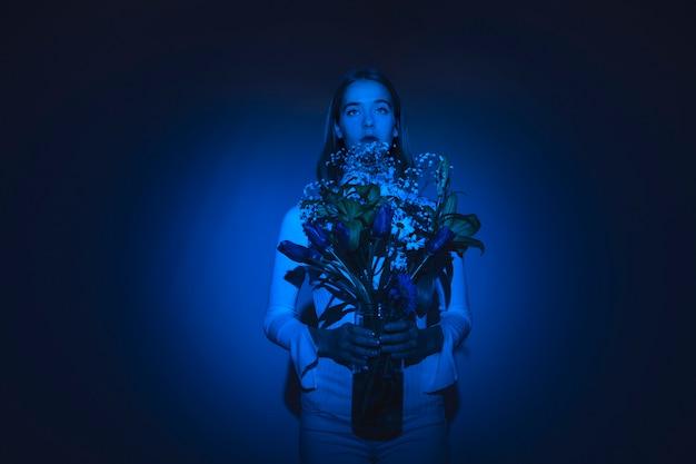 Mujer pensativa con flores en florero de vidrio