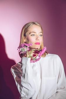Mujer pensativa con flores de gerbera en manga de camisa
