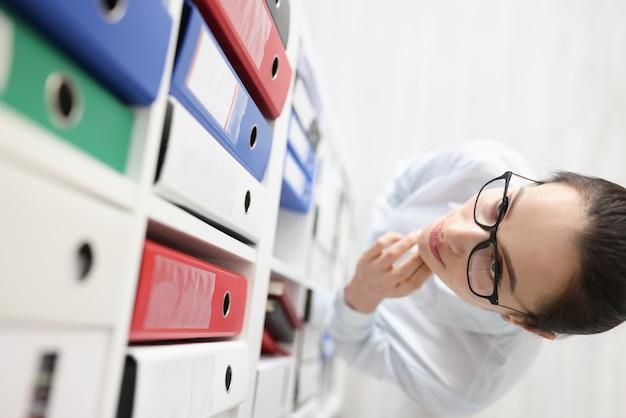 Mujer pensativa en gafas mira armario con carpeta de documentos