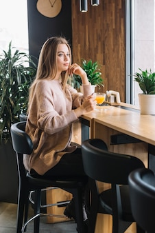 Mujer pensativa joven elegante que sostiene la taza de bebida en el contador de la barra en café