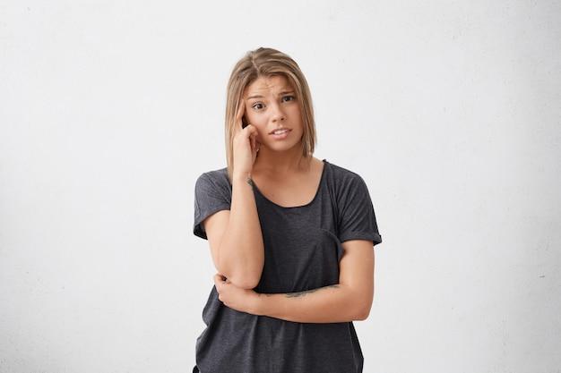 Mujer pensativa joven con estilo melancólico de pie frunciendo el ceño su rostro sosteniendo el dedo en la sien en confusión. mujer de raza mixta con peinado de moda expresando sus emociones