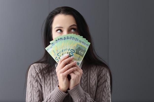 Mujer pensativa joven que sostiene un montón de billetes de euro delante de su concepto de compras de las mujeres