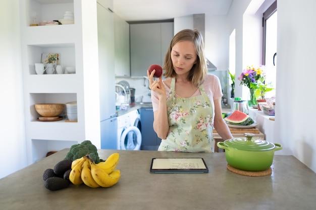 Mujer pensativa leyendo la receta en la almohadilla, sosteniendo la fruta mientras cocina en su cocina, usando la tableta cerca de una cacerola y verduras frescas en el mostrador. vista frontal. cocinar en casa y concepto de alimentación saludable.