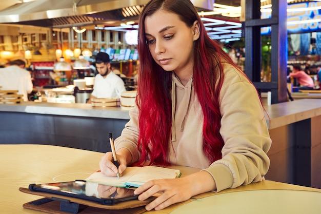 Una mujer pensativa con el pelo rojo trabaja a distancia en un café, escribe en un diario.