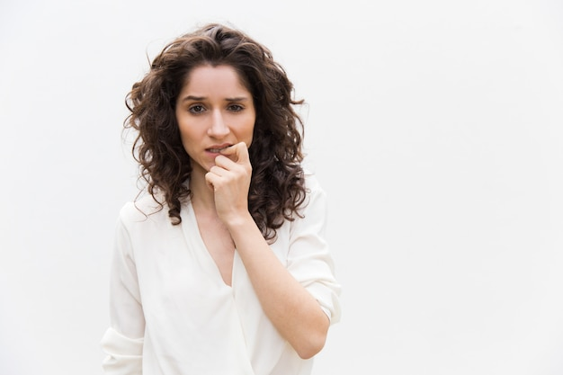 Mujer pensativa pensando y mordiendo los dedos