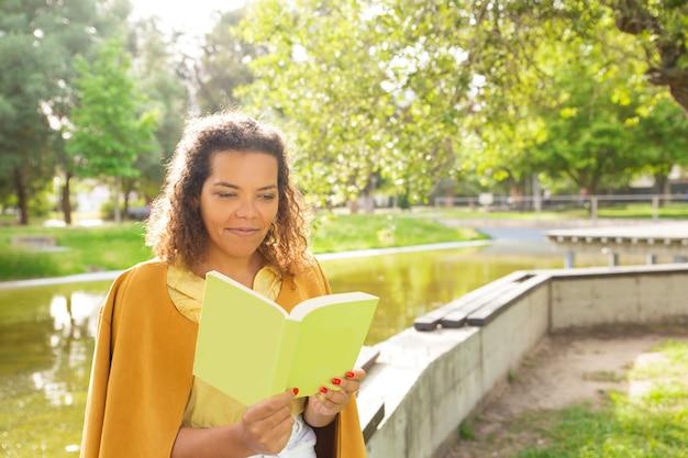 Mujer pensativa que disfruta leyendo en parque