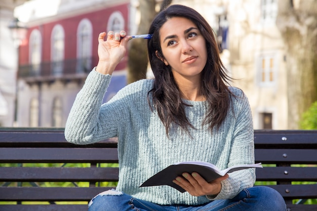 Mujer pensativa que rasguña la cabeza con la pluma y que se sienta en banco