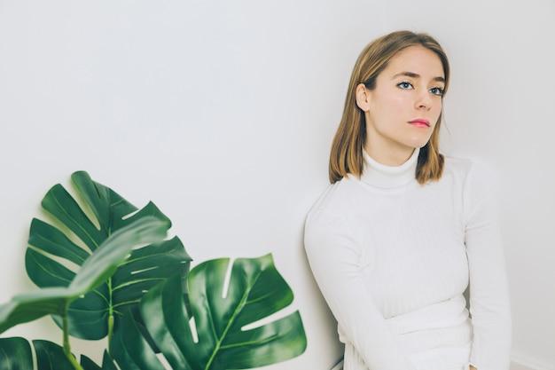 Mujer pensativa que se sienta cerca de la planta verde