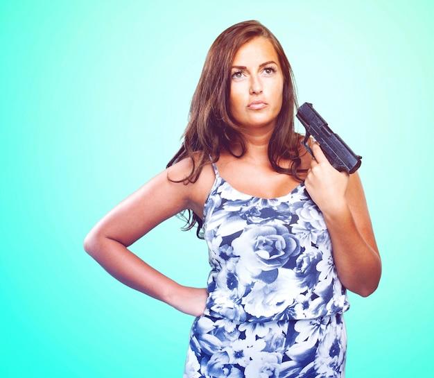 Mujer pensativa que sostiene un arma