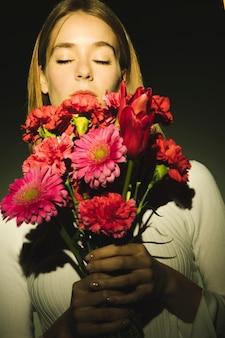 Mujer pensativa que sostiene el ramo de flores de color rosa