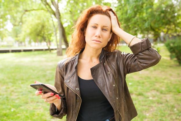 Mujer pensativa que sostiene el teléfono móvil, tocando la cabeza
