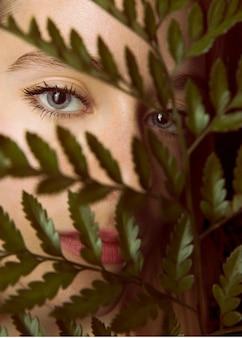 Mujer pensativa con rama de planta verde