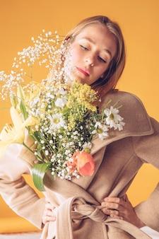Mujer pensativa con ramo de flores grandes en abrigo