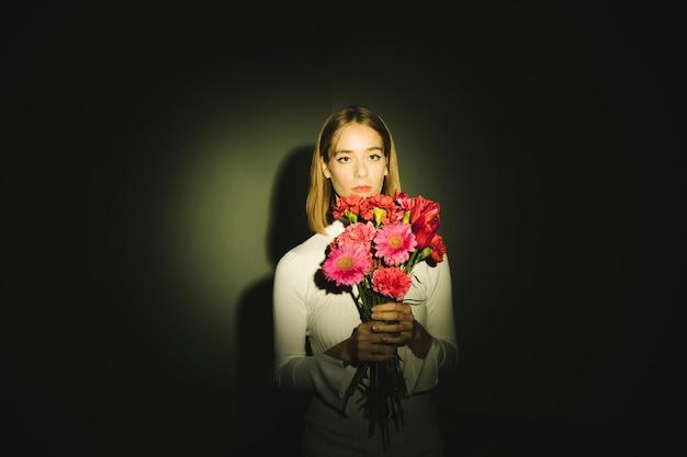 Mujer pensativa con ramo de flores.