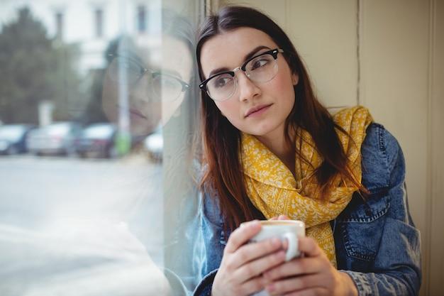 Mujer pensativa sentada con café en el café