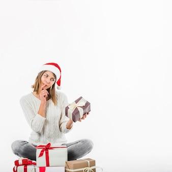 Mujer pensativa sentada con cajas de regalo