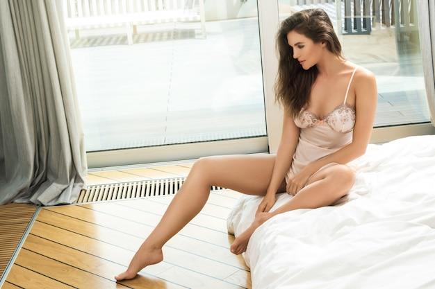 Mujer pensativa sentada en la cama