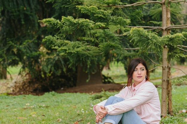 Mujer pensativa sentada en el césped cerca de árboles