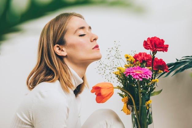 Mujer pensativa sentada con flores brillantes en florero