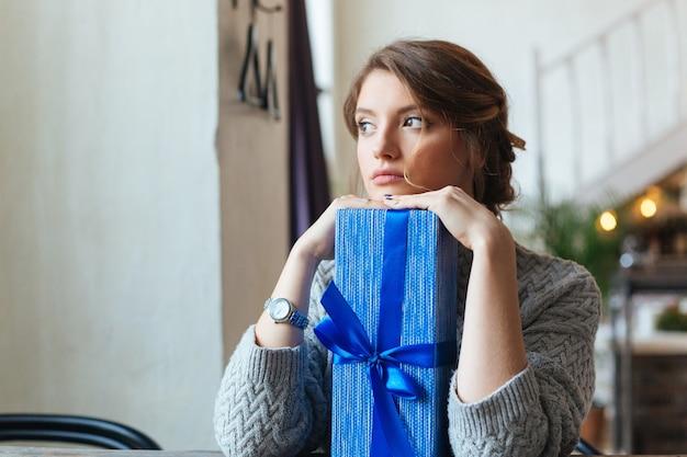 Mujer pensativa sentada en la mesa con caja de regalo y mirando a otro lado