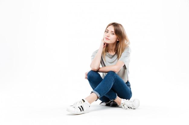 Mujer pensativa sentada con las piernas cruzadas