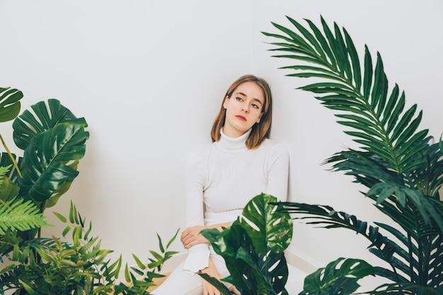 Mujer pensativa sentada en el piso con plantas verdes